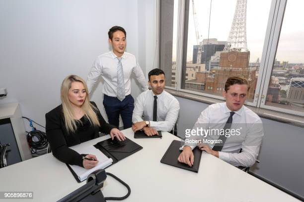 Female team leader and three male team members face the client at a meeting.
