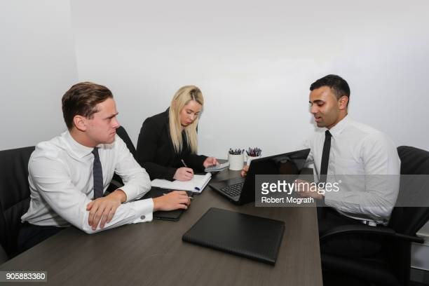 Female team leader and two male team members confer to discuss strategy and consider figures.