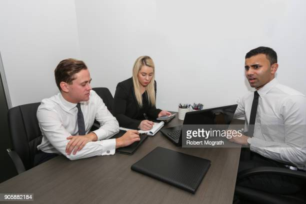 Female team leader and two male team members consider strategy and express worry about results.