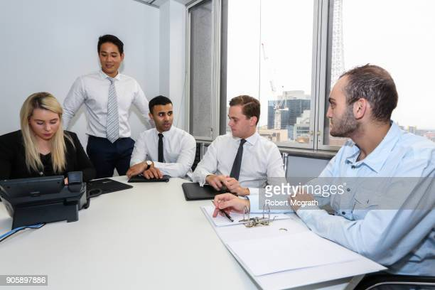 Female team leader consider a strategy, while three team members discuss options and offer suggestions during a client meeting.
