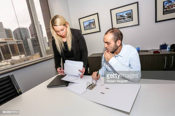 Female team leader goes hrough papers as she explains options with a client.