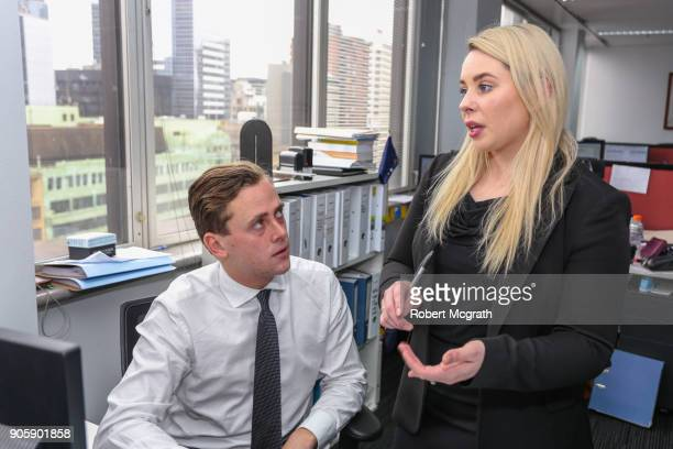 Female team member explains to a male team member, ihow to implement decisons  made at a meeting.