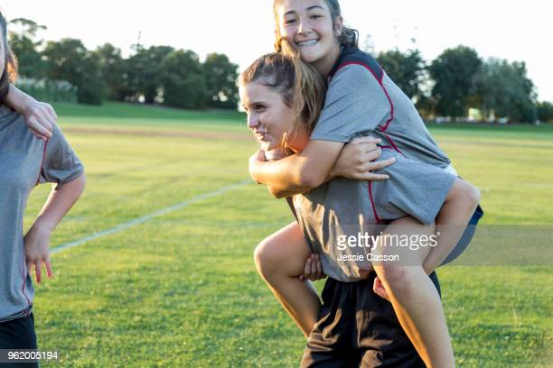 Female team players piggy backing on sports field