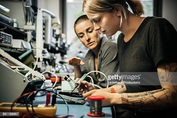 female technician guiding young trainee - leanincollection stock pictures, royalty-free photos & images