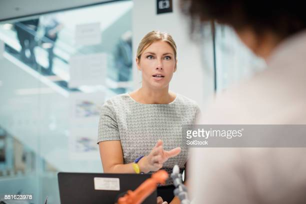 female technician in control of a meeting - assertiveness stock pictures, royalty-free photos & images