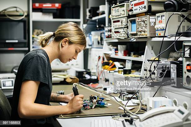 Female Technician Repairing Electronical Device