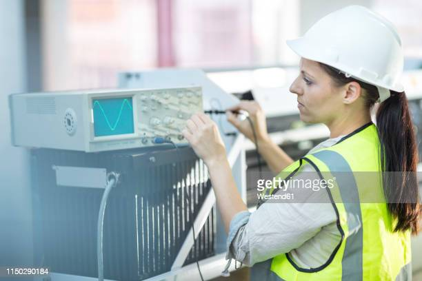 female technician working on oscilloscope - oscilloscope stock pictures, royalty-free photos & images