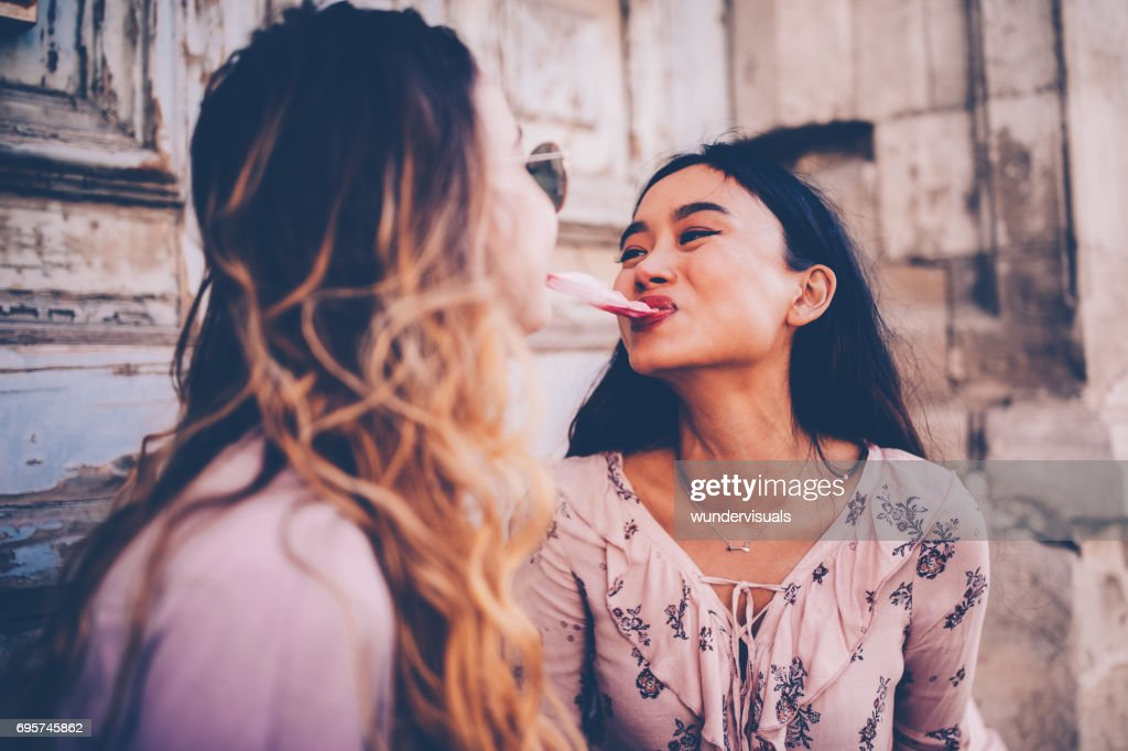 Female Teenage Girls With Chewing Gum In Antique City Street Stock Photo
