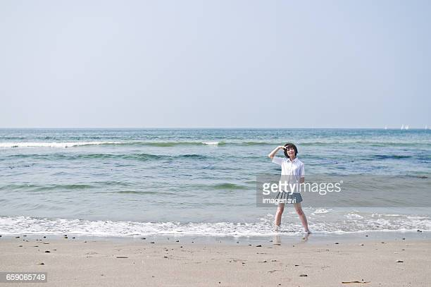 Female teenage student in uniform standing at beach