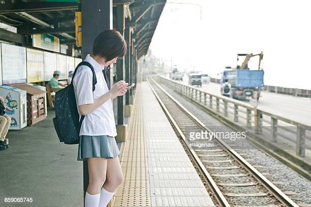 Female teenage student in uniform using smartphone at platform