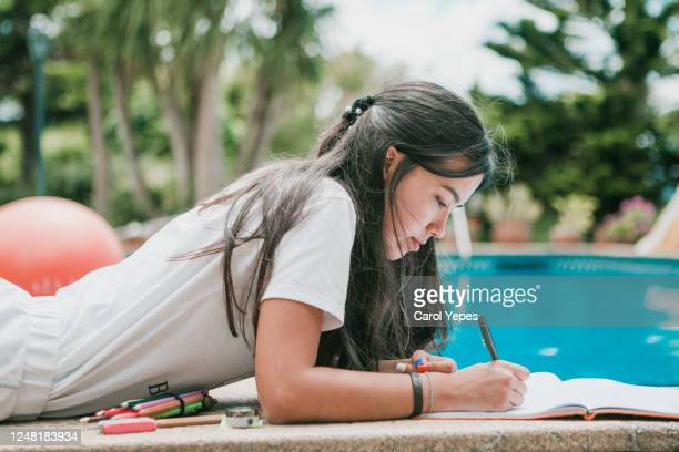 female teenager doing homeworks in back yard in a sunny day - text schriftsymbol stock-fotos und bilder