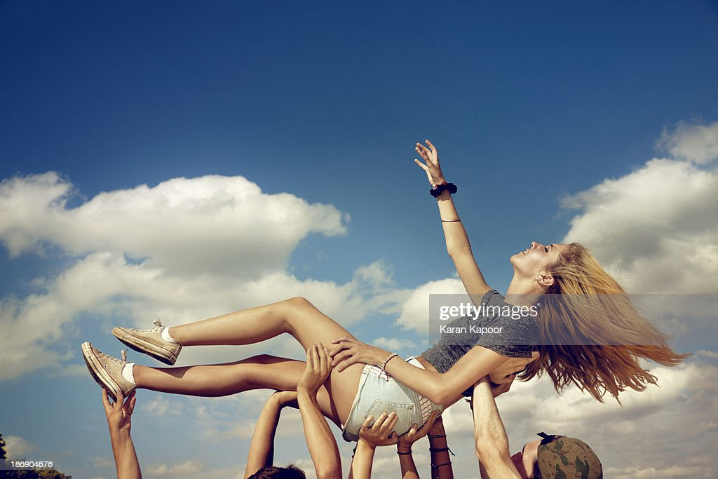 Female teenager held up triumphantly : Stock Photo