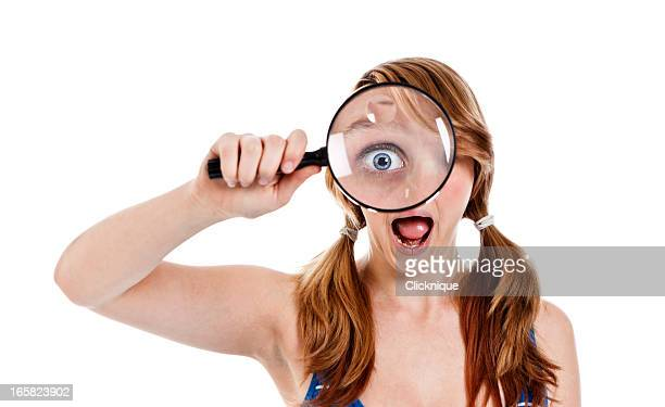 female teenager holding a magnifying glass to her eye - big eyes stock photos and pictures
