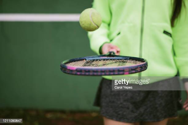 female teenager holding tennis ball and racket - racket sport stockfoto's en -beelden