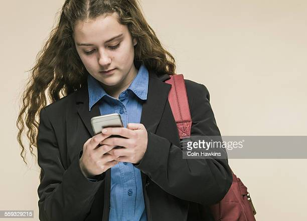 female teenager in school uniform using mobile pho - colin hawkins stock pictures, royalty-free photos & images