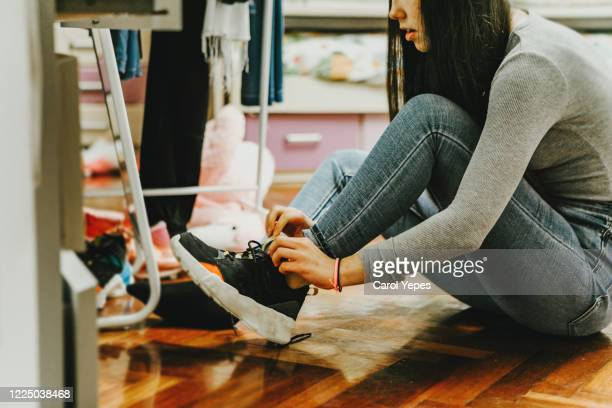 female teenager putting shoes on at home to go out - snow boot stock pictures, royalty-free photos & images