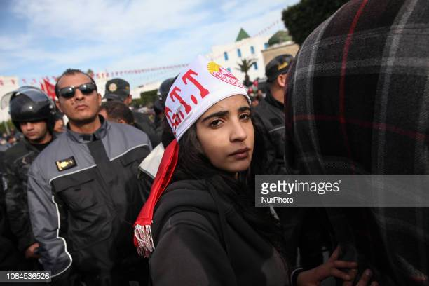 Female teenager seen in front security forces members as she took part in a rally held at the Government square in the Kasbah in Tunis on January 17...