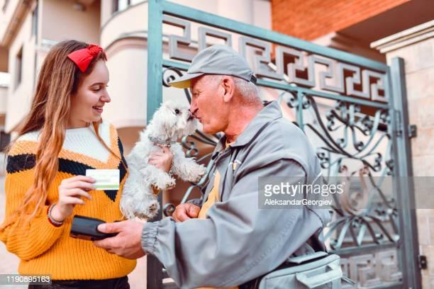 female teenager using credit card to pay senior mailman for service who kisses dog - carteiro imagens e fotografias de stock