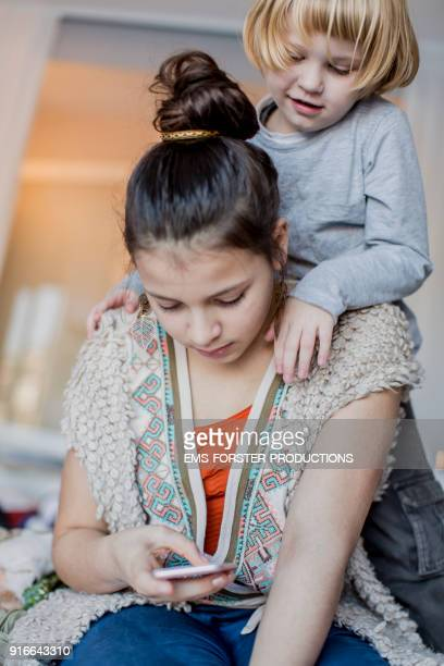 female teenager using mobile phone with her little brother indoors
