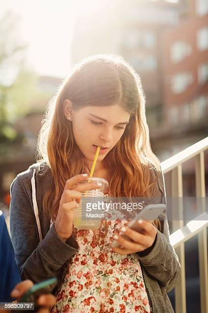 Female teenager using smart phone while drinking juice outdoors
