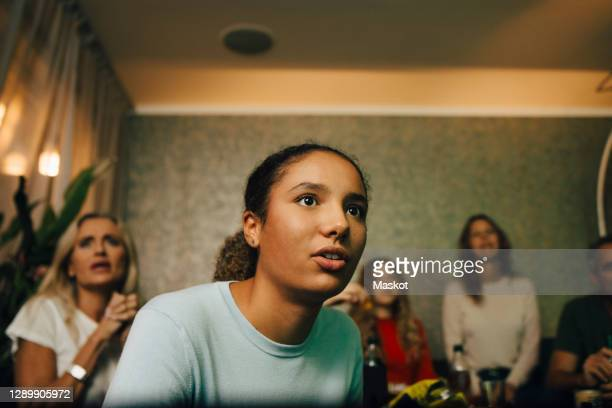 female teenager watching sports with family at night - supporter stock pictures, royalty-free photos & images