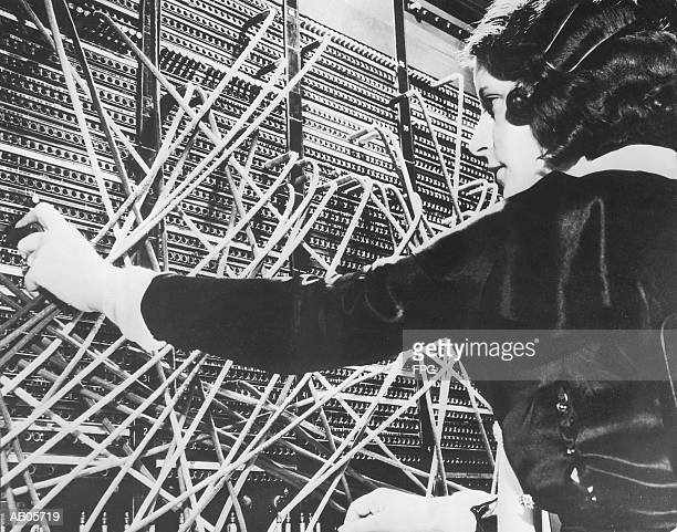 Female telephone switchboard operator connecting caller, close-up (B&W
