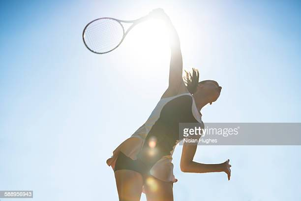 female tennis player about to hit a serve - tenis fotografías e imágenes de stock