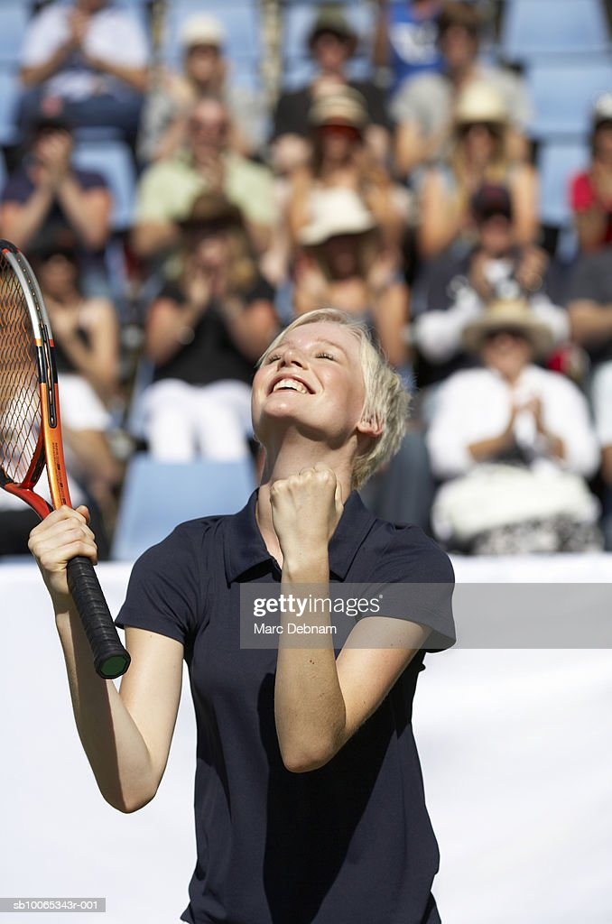 Female tennis player celebrating victory on outdoor court : Foto stock