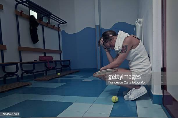 Female tennis player crouching in the locker room