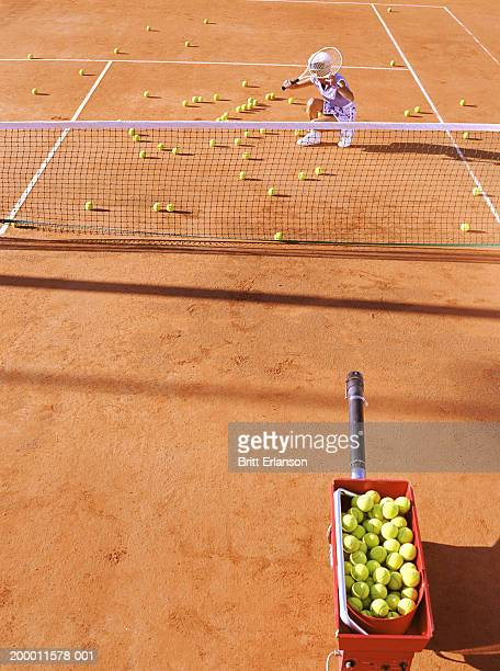Female tennis player guarding face with racquet on court