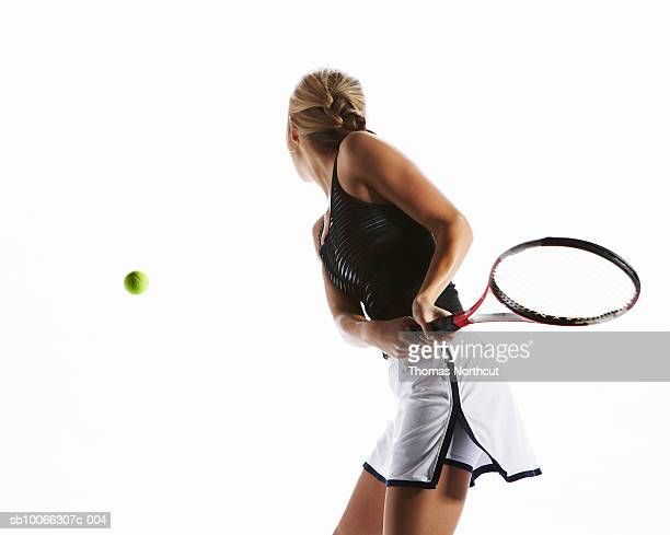 Female tennis player hitting backhand shot, rear view