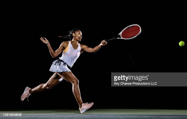 female tennis player hitting running forehand shot - tennis player stock pictures, royalty-free photos & images