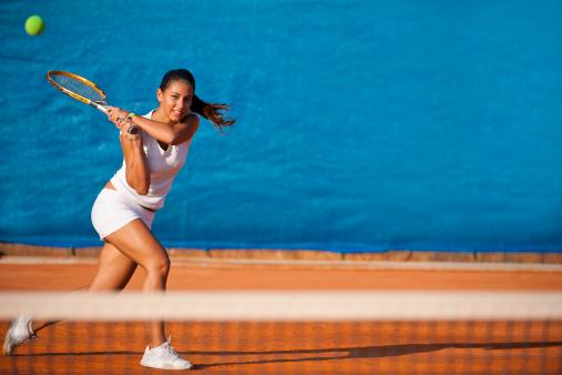 Female tennis player hitting the ball 155095819