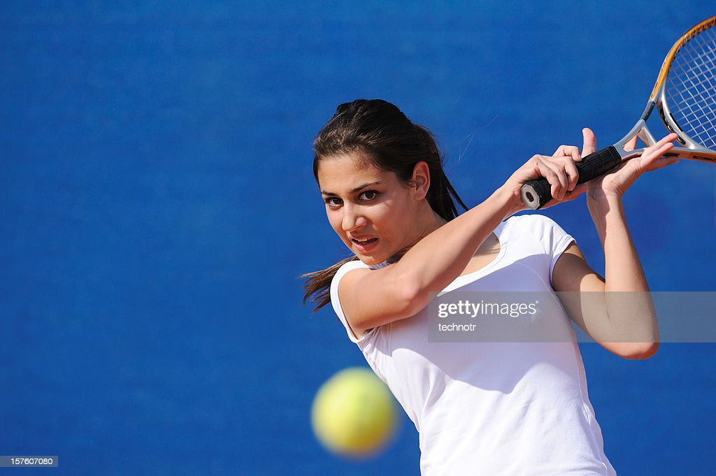 Female tennis player hitting the ball : Stock Photo