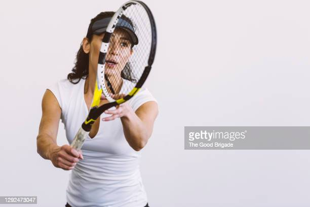female tennis player holding racket against white background - serving sport stock pictures, royalty-free photos & images