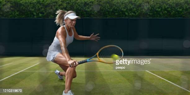 tennisspielerin in mid motion während grass court spiel - damen volleyball stock-fotos und bilder