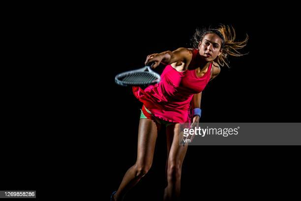 female tennis player in mid swing - tennis player stock pictures, royalty-free photos & images