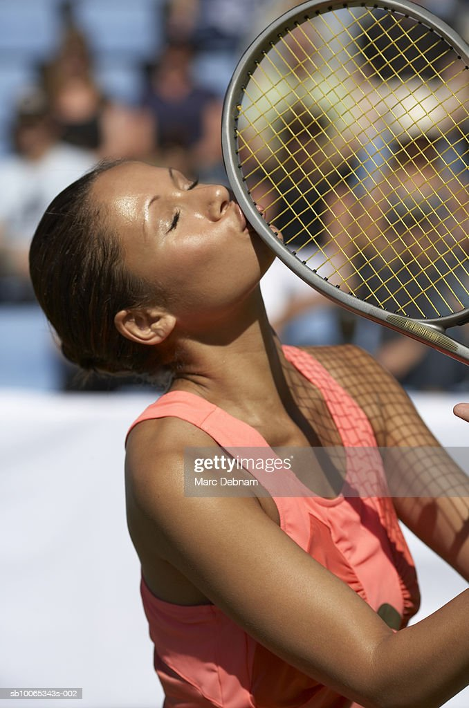 Female tennis player kissing racket, outdoors : Foto stock
