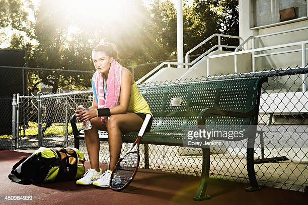 Female tennis player on bench resting