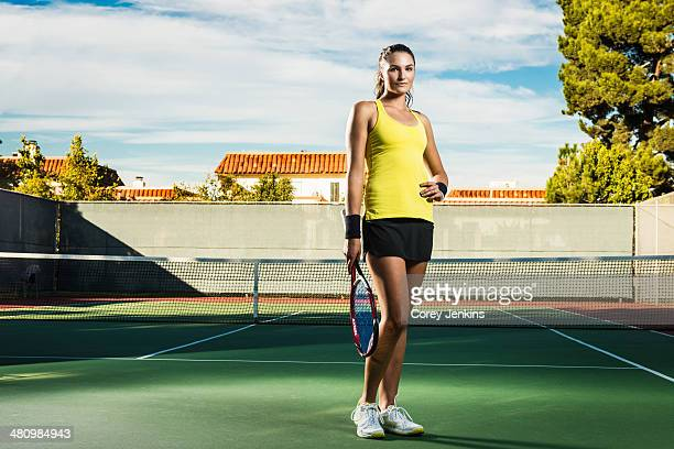 Female tennis player on court holding racket