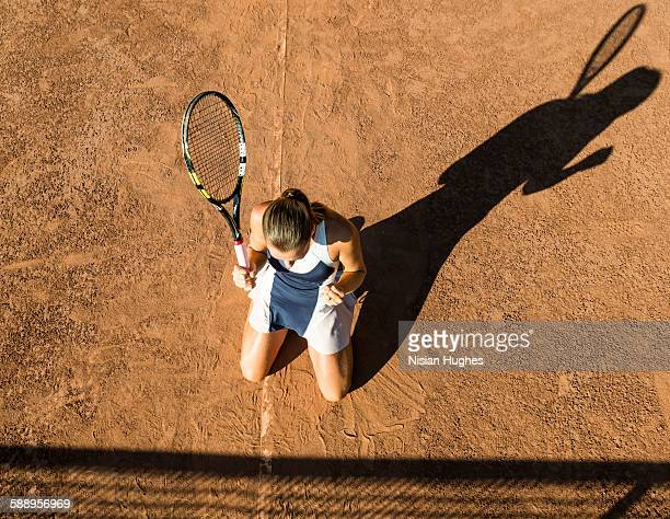 Female tennis player on knees celebrating victory