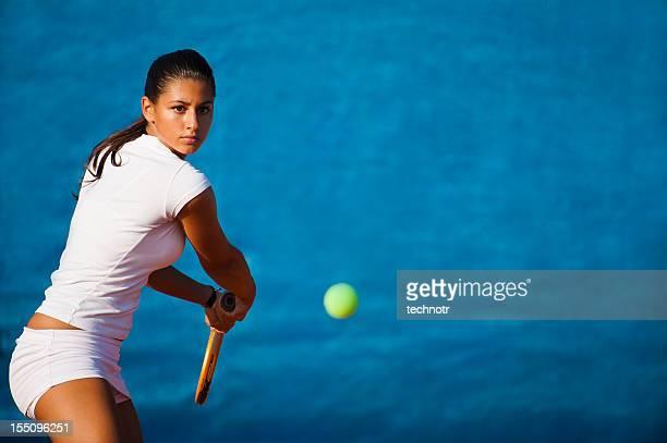 女性テニスプレーヤー、青色背景