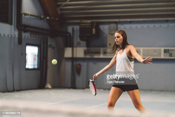 female tennis player playing tennis indoors - racquet stock pictures, royalty-free photos & images