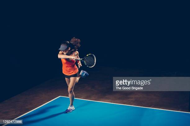 female tennis player practicing on court against black background - tennis stock pictures, royalty-free photos & images