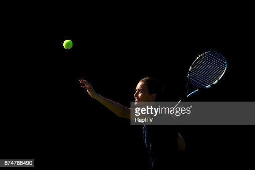 A Female Tennis Player Releases the Ball to Serve.