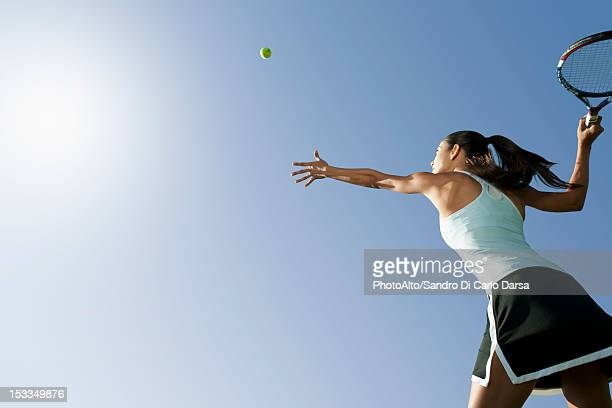 female tennis player serving ball, low angle view - tennis stock-fotos und bilder