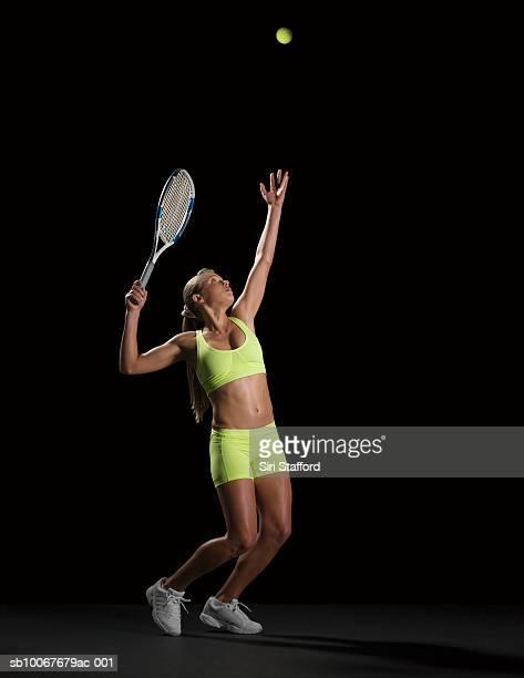 female tennis player serving ball, studio shot - serving sport stockfoto's en -beelden
