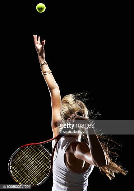 Female tennis player serving, rear view