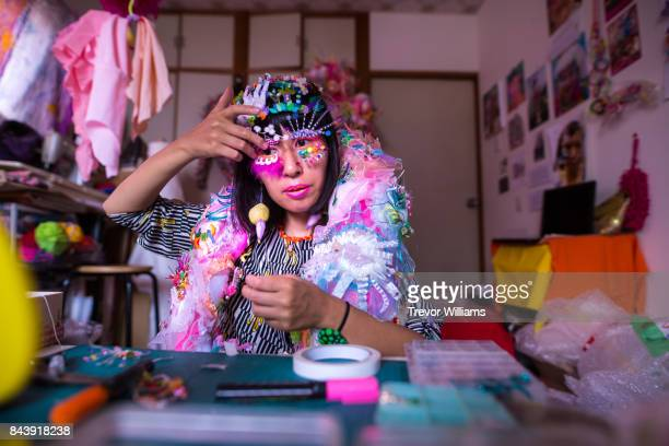 a female textile artist preparing and adorning a colorful costume and applying make-up - cosplay stock pictures, royalty-free photos & images
