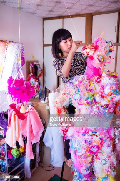 A female textile artist working in her colorful studio